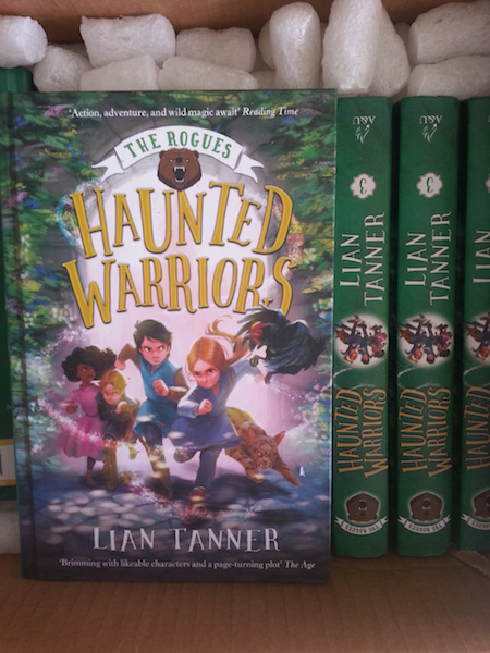 Box full of copies of Haunted Warriors by Lian Tanner